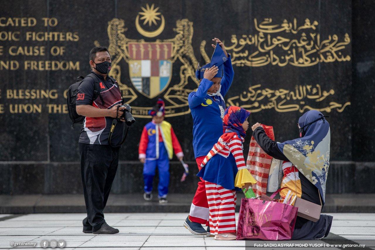 Mohd Noor Shahril dan isteri membawa anak mereka, Ahmad Najeh Syauqi, 12, Ahmad Najid Saufi, 9, dan Naa'ilah Sofiyyah, 5 tahun ke Tugu Negara untuk bergambar bersama busana khas sempena hari kemerdekaan ke-64, di Kuala Lumpur. - Gambar Sadiq Asyraf