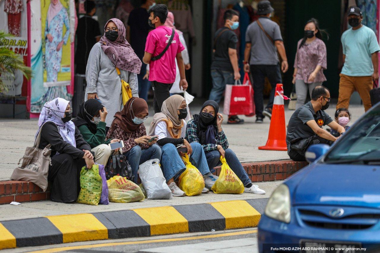 Sekumpulan pembeli-belah duduk berehat di tepi jalan. - Gambar oleh Azim Rahman