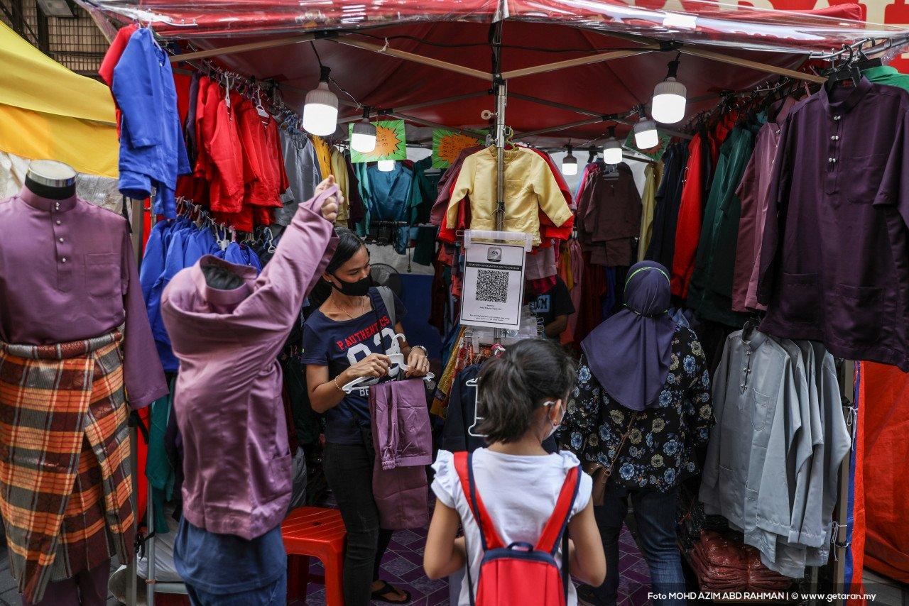 Satu keluarga membelek pakaian di gerai untuk persiapan raya. - Gambar oleh Azim Rahman
