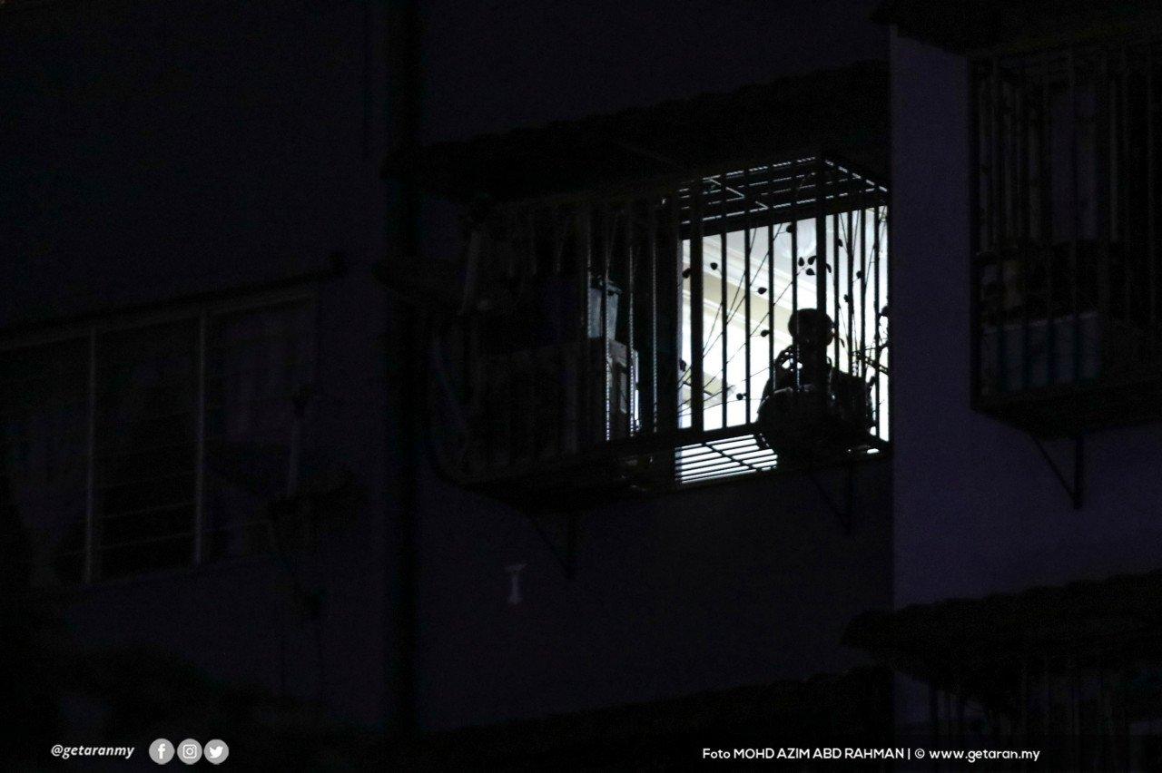 Kelihatan kelibat seorang penduduk Pangsapuri Sri Penara di tingkap yang terpaksa berkurung di rumah kerana perlaksanaan PKPD.