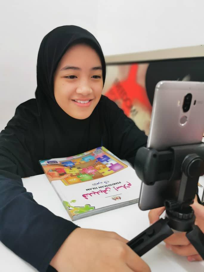 Anak kepada Siti Hajar, Aisy Zahra Mohd Omar Faizie, 11, menggunakan telefon pintar ketika menjalani PdPR.
