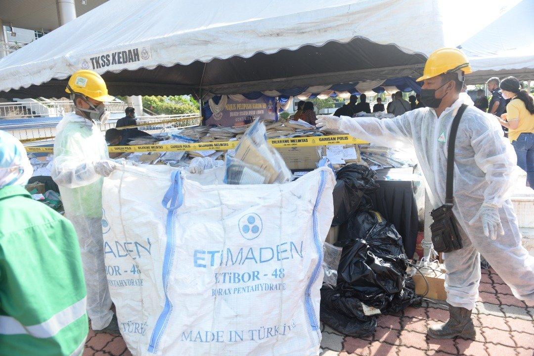 Petugas syarikat swasta memasukkan dadah-dadah yang akan dilupuskan ke dalam guni selepas sidang akhbar di IPK Kedah, hari ini.